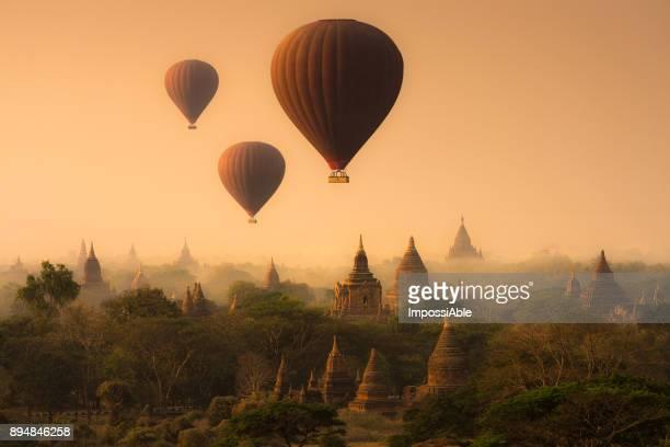hot air balloon flying over old antique pagodas in bagan, myanmar - myanmar fotografías e imágenes de stock