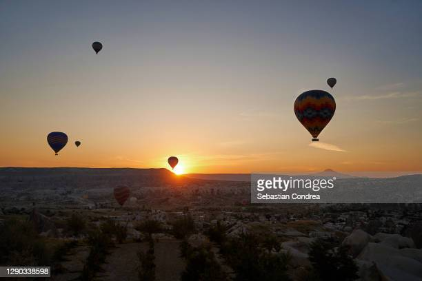 hot air balloon flying over rock cave mountain and city at cappadocia, turkey. - royal tour stock pictures, royalty-free photos & images