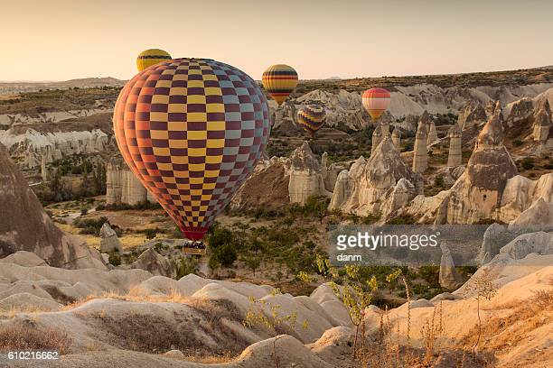 hot air balloon flying over rock landscape at cappadocia turkey - capadocia fotografías e imágenes de stock
