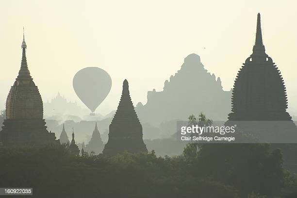 CONTENT] A hot air balloon full of tourists drifts silently at sunrise between the thousands of ancient pagodas temples and stupas most of which date...