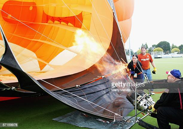 Hot air balloon 'Honey Bear' pilot Ryan 'Rowdey' Smith of America blasts hot air into his balloon to inflate it during a wet Mass Ascension on day...