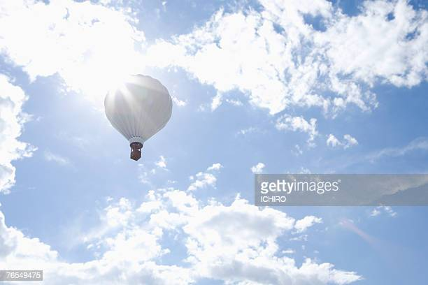 Hot air balloon in cloudy sky, low angle view