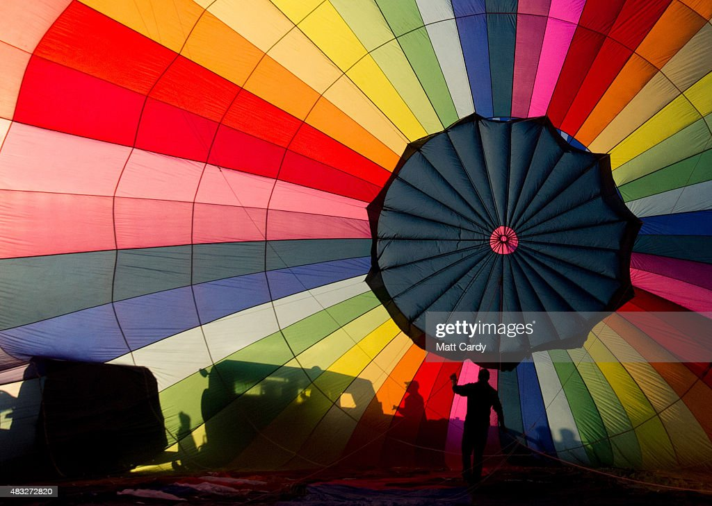 A hot air balloon is inflated at the Bristol International Balloon Fiesta main arena at the Ashton Court estate on August 7, 2015 in Bristol, England. The early morning flight of over 100 balloons was the first mass ascent of the four-day Bristol International Balloon Fiesta which started yesterday. Now in its 37th year, the Bristol International Balloon Fiesta is Europe's largest annual hot air balloon event in the city that is seen by many balloonists as the home of modern ballooning.