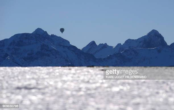A hot air balloon is pictured as it hovers over the Alps near Rueckholz southern Germany on January 24 2018 / AFP PHOTO / dpa / KarlJosef Hildenbrand...