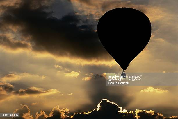 A hot air balloon is silhouetted against the sunset clouds during the Northampton Balloon Festival on 20h August 2000 at the Billing Aquadrome in...