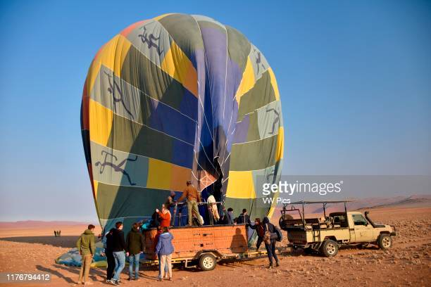 Hot air balloon lands on top of a car in the Namib Desert. Sossusvlei area. Sesriem. Namibia.