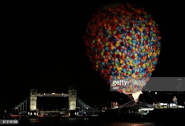 A hot air balloon made up of lots of smaller balloons and tied to a barge is inflated before being flown under Tower Bridge in central London on...