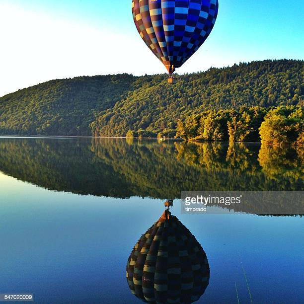 hot air balloon over a lake in auvergne, france - auvergne stock pictures, royalty-free photos & images