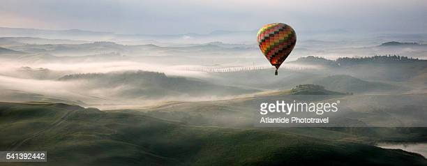 hot air balloon over crete senesi area of tuscany - hot air balloon stock pictures, royalty-free photos & images