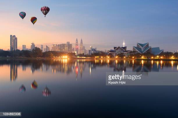 hot air balloon over kuala lumpur skyline, titiwangsa park in malaysia. - south east asia stock pictures, royalty-free photos & images