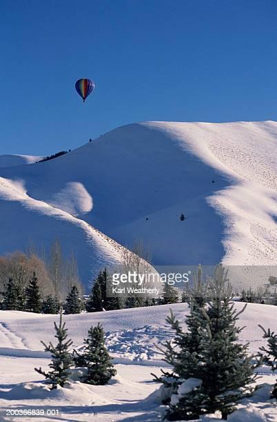 hot air balloon over snowy mountains,  sun valley, idaho, usa - sun valley idaho stock photos and pictures