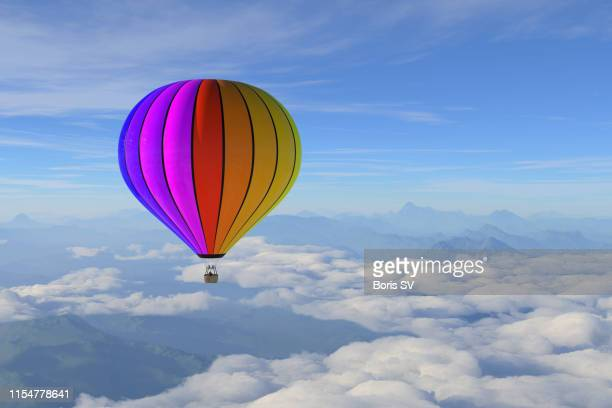 hot air balloon over the mountain range - balloon ride stock pictures, royalty-free photos & images