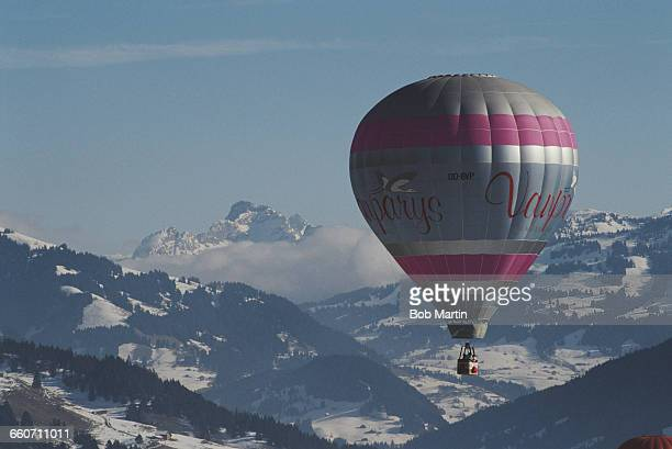 Hot air balloon rises over snow capped mountains in Gstaad for a balloon festival the Gstaad International Balloon Fiesta on 1 January 1991 near...