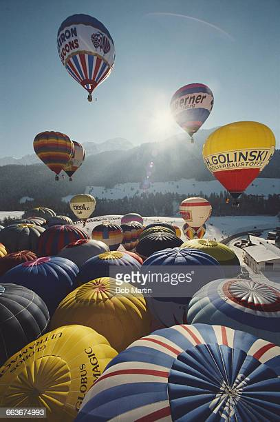 Hot air balloon rises over snow capped mountains in Gstaad for the Gstaad International Balloon Fiesta on 1 January 1991 near Gstaad Switzerland