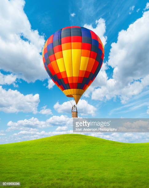 Hot Air Balloon Vertical Rising Over Grassy Hills