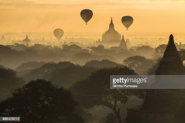 hot air balloons above pagodas in bagan, mandalay, myanmar - association of southeast asian nations stock pictures, royalty-free photos & images