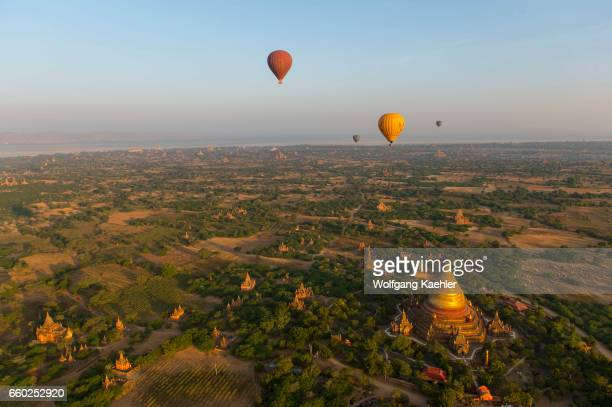 Hot air balloons are flying over the Dhammayazika Pagoda in Bagan Myanmar in the early morning