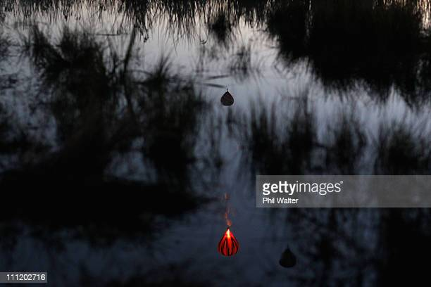 Hot air balloons are reflected in the Hamilton lake after leaving from Innes Common at dawn on the second day of the Balloons Over Waikato Hot Air...