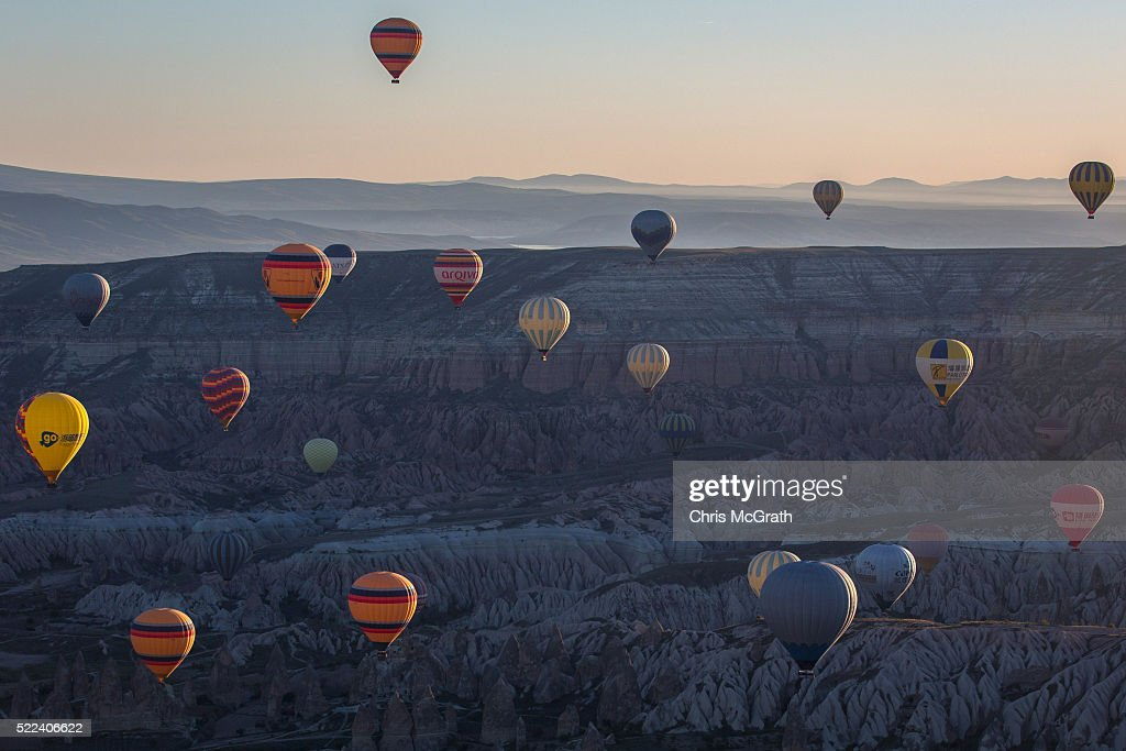 Hot air balloons are seen over rock formations near the town of Goreme on April 17, 2016 in Nevsehir, Turkey. Cappadocia, a historical region in Central Anatolia dating back to 3000 B.C is one of the most famous tourist sites in Turkey. Listed as a World Heritage Site in 1985, and known for its unique volcanic landscape, fairy chimneys, large network of underground dwellings and some of the best hot air ballooning in the world, Cappadocia is preparing for peak tourist season to begin in the first week of May. Despite Turkey's tourism downturn, due to the recent terrorist attacks, internal instability and tension with Russia, local vendors expect tourist numbers to be stable mainly due to the unique activities on offer and unlike other tourist areas in Turkey such as Antalya, which is popular with Russian tourists, Cappadocia caters to the huge Asian tourist market.