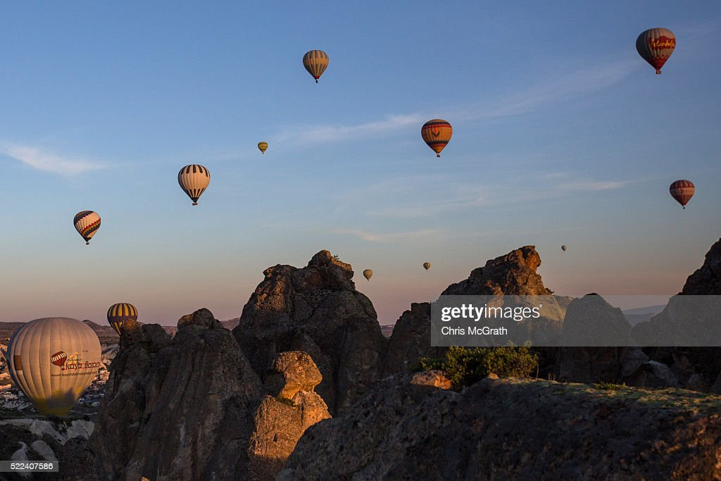 Hot air balloons are seen over rock formations on April 18, 2016 in Nevsehir, Turkey. Cappadocia, a historical region in Central Anatolia dating back to 3000 B.C is one of the most famous tourist sites in Turkey. Listed as a World Heritage Site in 1985, and known for its unique volcanic landscape, fairy chimneys, large network of underground dwellings and some of the best hot air ballooning in the world, Cappadocia is preparing for peak tourist season to begin in the first week of May. Despite Turkey's tourism downturn, due to the recent terrorist attacks, internal instability and tension with Russia, local vendors expect tourist numbers to be stable mainly due to the unique activities on offer and unlike other tourist areas in Turkey such as Antalya, which is popular with Russian tourists, Cappadocia caters to the huge Asian tourist market.