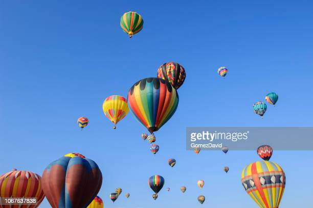 hot air balloons ascending into cloudy sky - balloon fiesta stock pictures, royalty-free photos & images