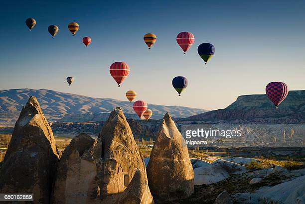 Hot air balloons at sunrise flying over Cappadocia, Goreme, Turkey