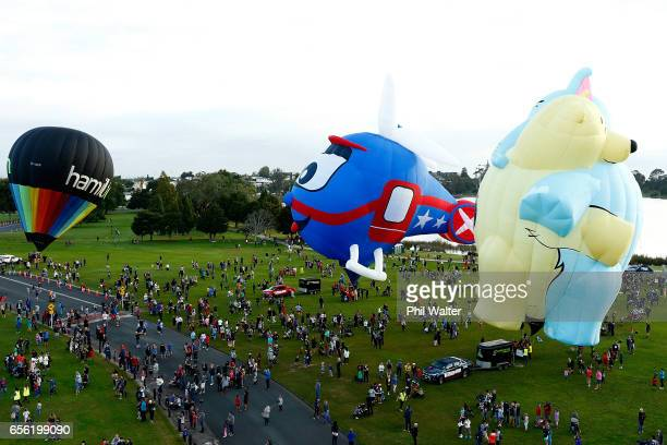 Hot air balloons begin to take to the air over the Hamilton Lake during the Mass Ascension on the opening day of Balloons Over Waikato on March 22,...