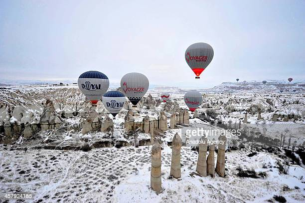 Hot air balloons flly over the famous volcanic rock formations around Goreme on December 15 2013