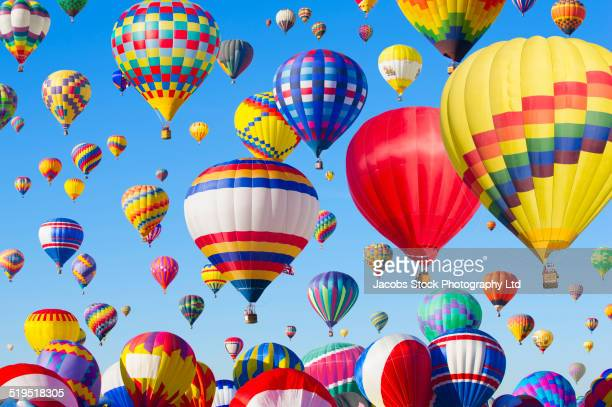 hot air balloons floating in blue sky - balloon ride stock pictures, royalty-free photos & images