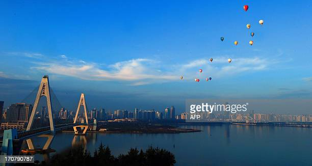 Hot air balloons fly across Qiongzhou Strait in Haikou, south China's Hainan province during the H1 China Hot Air Balloon Challenge on June 18, 2013....
