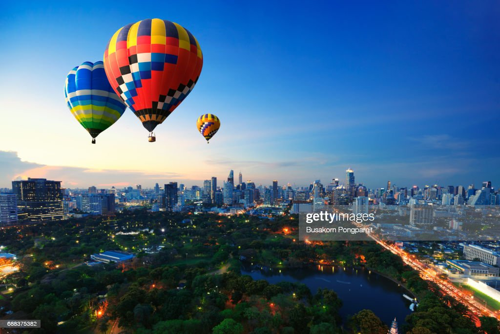 Hot air balloons fly over cityscape at sunset background : Stock Photo