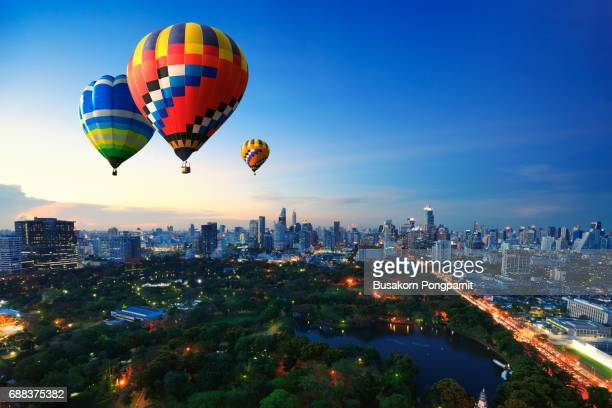 Hot air balloons fly over cityscape at sunset background