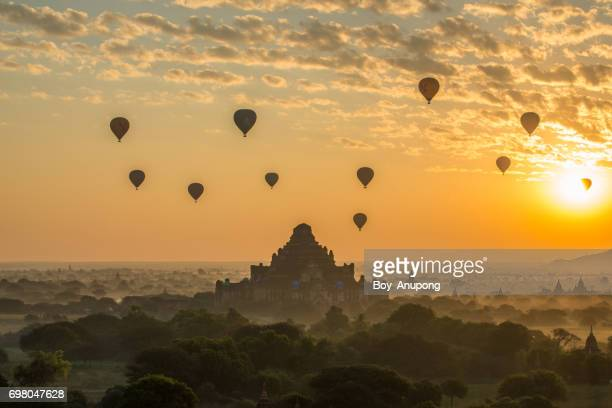 Hot air balloons fly over Dhammayangyi temple the largest temple on the plains of Bagan.
