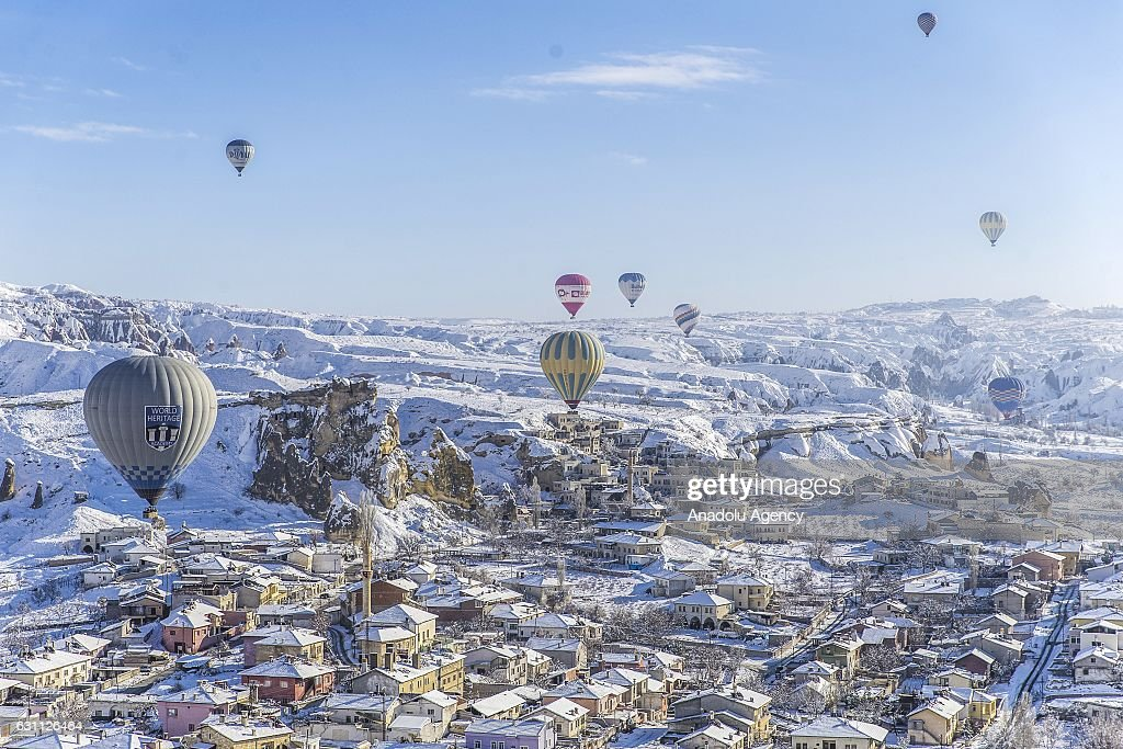 Hot air balloons fly over snow covered Cappadocia, a historical region in Central Anatolia, largely in Nevsehir Province, known for the fairy chimneys, during the winter season on January 06, 2017 in Nevsehir, Turkey.
