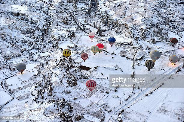 Hot air balloons fly over the famous volcanic rock formations during the winter season in Cappadocia a historical region in central Anatolia in...