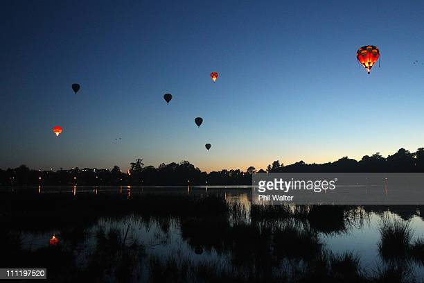Hot air balloons fly over the Hamilton lake after leaving from Innes Common at dawn on the second day of the Balloons Over Waikato Hot Air Balloon...