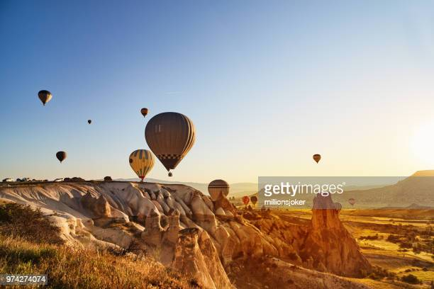 hot air balloons flying at sunset, cappadocia, turkey - hot air balloon stock pictures, royalty-free photos & images