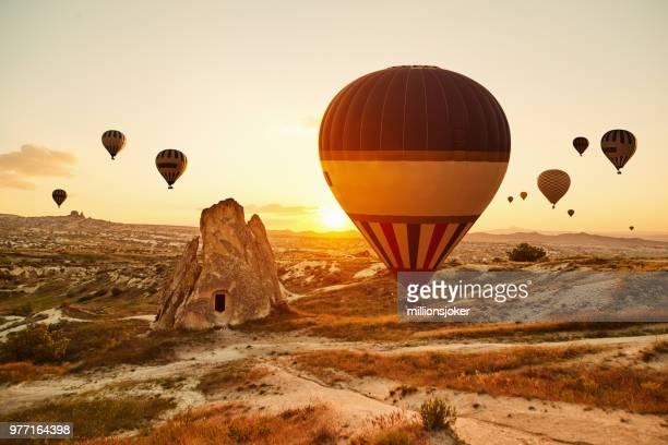 hot air balloons flying at sunset, cappadocia, turkey - cappadocia stock pictures, royalty-free photos & images