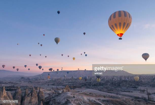 hot air balloons flying in red and rose valley in goreme in cappadocia in turkey - hot air balloon stock pictures, royalty-free photos & images