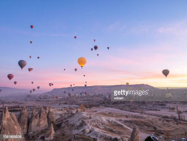 hot air balloons flying in red and rose valley in goreme in cappadocia in turkey - cappadocia stock pictures, royalty-free photos & images