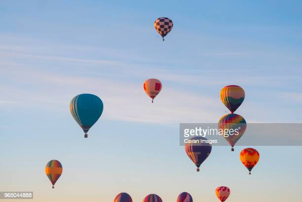 hot air balloons flying in sky - hot air balloon stock pictures, royalty-free photos & images