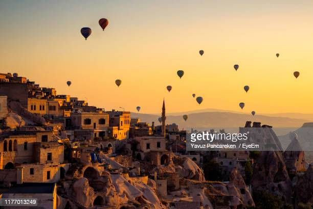 hot air balloons flying over buildings in city during sunset - balloon fiesta stock pictures, royalty-free photos & images