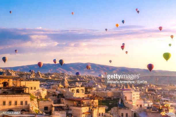 hot air balloons flying over buildings in city - カッパドキア ストックフォトと画像