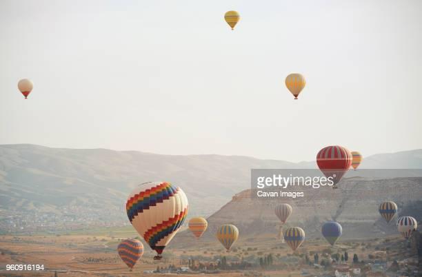 hot air balloons flying over cappadocia - balloon fiesta stock pictures, royalty-free photos & images