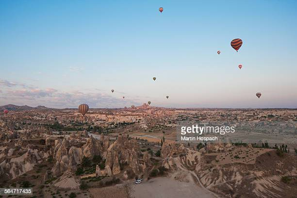Hot air balloons flying over dramatic landscape