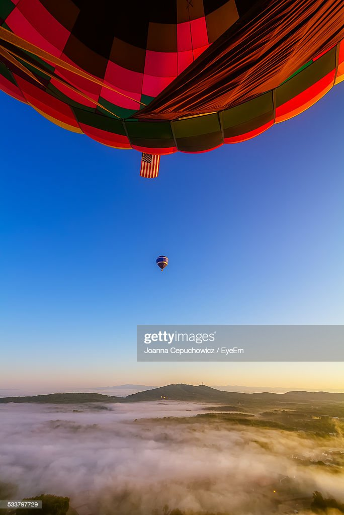 Hot Air Balloons Flying Over Foggy Mountains Against Clear Blue Sky : Foto stock