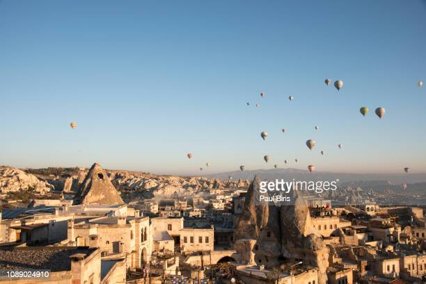 hot air balloons flying over goreme at sunrise, cappadochia, turkey - editorial stock pictures, royalty-free photos & images