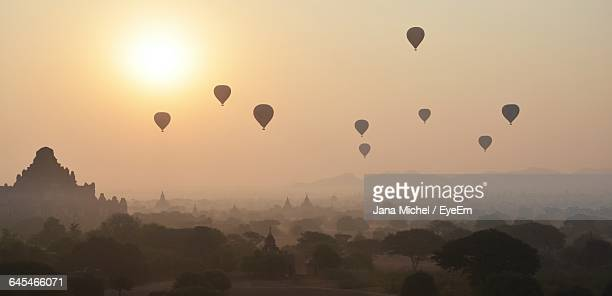 Hot Air Balloons Flying Over Historic Temples Against Sky At Morning