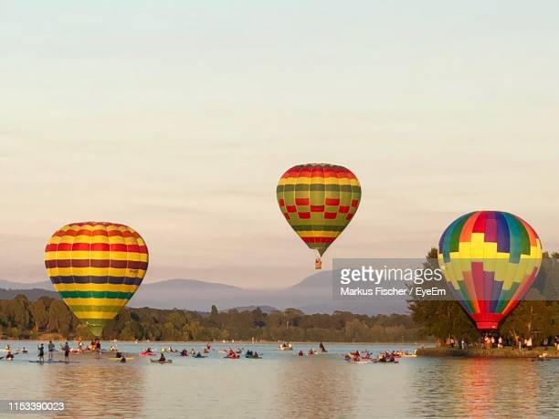 hot air balloons flying over lake against sky during sunset - canberra photos et images de collection