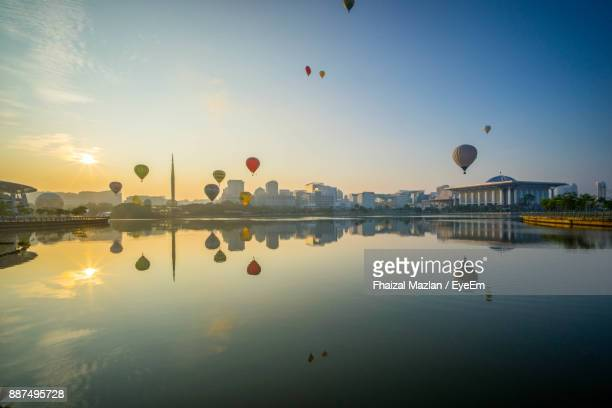 hot air balloons flying over lake - putrajaya stock photos and pictures